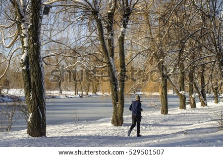 jogging girl in the background of winter morning landscape with the frozen pond