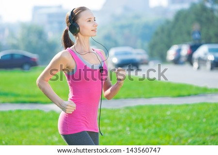 Jogging woman running in city park in sunshine on beautiful summer day and listening a music in headphones. Sport fitness model caucasian ethnicity training outdoor for marathon.
