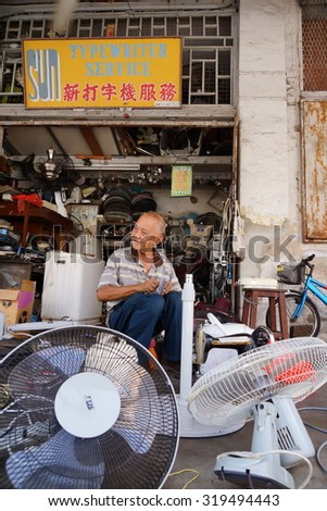 JOHOR, MALAYSIA - FEB 02: An old man at in front of his typewriter service shop on February 2, 2013. He is expertise in repairing fan, typewrite, rice cooker, sewing machine and those electrical stuff