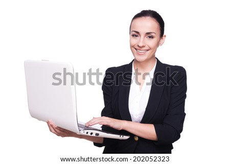 Join a digital age! Beautiful young woman in formalwear working on laptop and smiling, isolated on white background