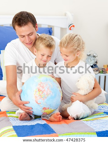 Jolly father and his children holding a terrestrial globe sitting on a bed