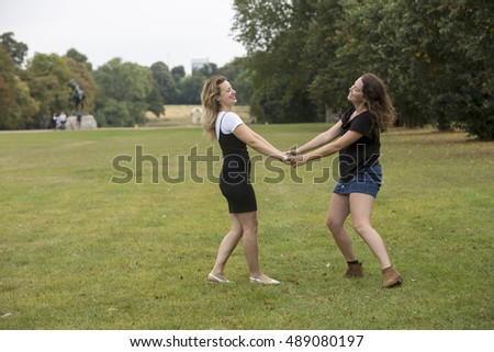 Joy. Two young women are twirling around in the park, happy in the warmth of a delightful summer's day.