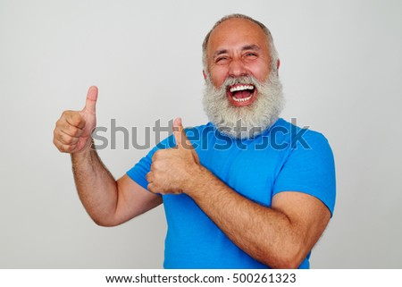 Joyful aged man is smiling sincerely and giving two thumbs up against white background