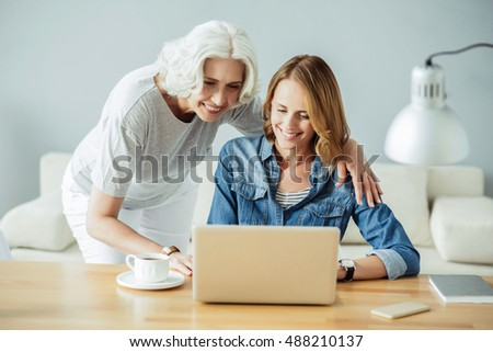 Joyful beautiful woman using laptop