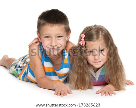 Joyful boy and a smiling girl are lying together on the white background