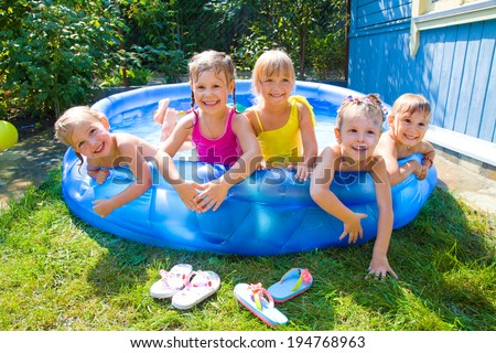Joyful Children playing in inflatable pool