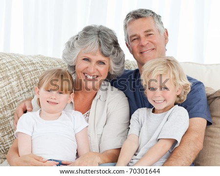Joyful family looking at the camera at home