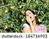 Joyful female farmer eating pear from tree outdoor. Woman enjoying the taste of healthy natural fruit. - stock photo