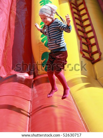 Joyful girl jumps on inflatable attractions