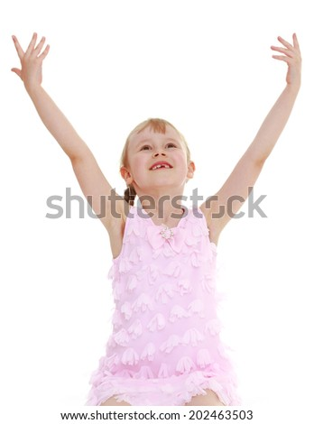 Joyful girl raised her hands up.Photo in kindergarten,active lifestyle,happiness concept,carefree childhood concept.