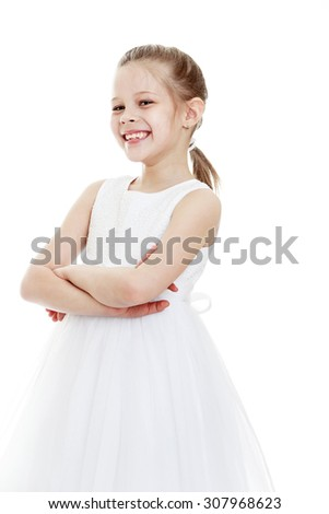 Joyful little girl of school age in a white long translucent dress. The girl placed her hands on his chest . Closeup-Isolated on white background