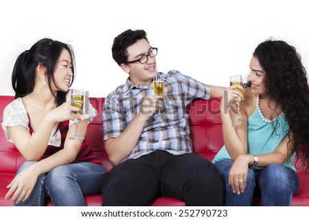 Joyful multi ethnic people sitting on couch while drinking beer together, isolated on white background