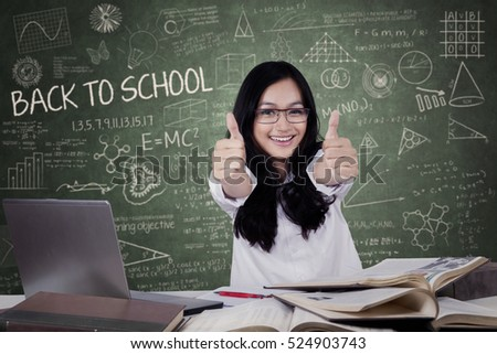 Joyful teenage student with black hair back to school and show thumbs up in the class