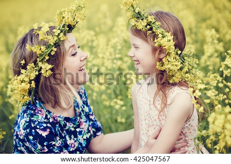 joyful woman little girl in flower garland at yellow field