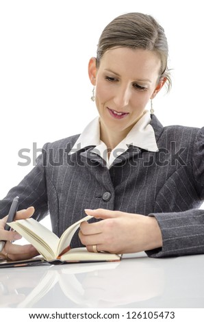 Joyful woman looking in her diary. Isolated over white background.