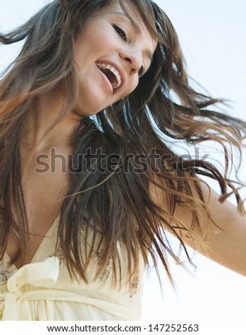 Joyful young woman flicking her hair in the air against a blue sky, smiling and feeling joyful and free and having fun during a sunny day.