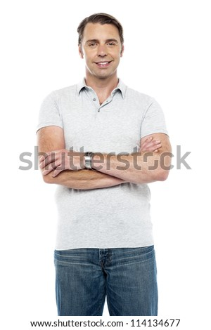 Joyous young man posing with his arms crossed isolated over white background