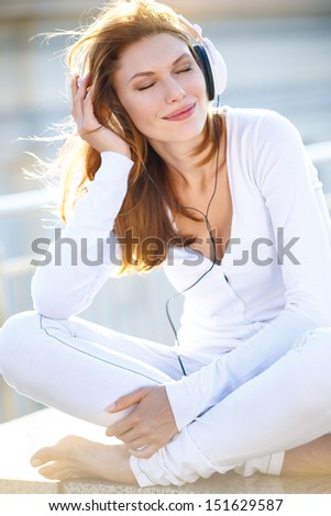 Joyous young woman listens to music through headphones / smiling brunette girl in white clothes enjoy stereo sound with eyes closed
