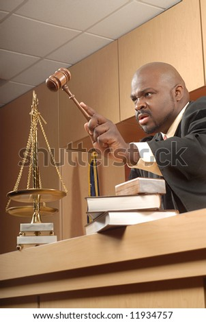 Judge banging his gavel and trying to bring the courtroom to order
