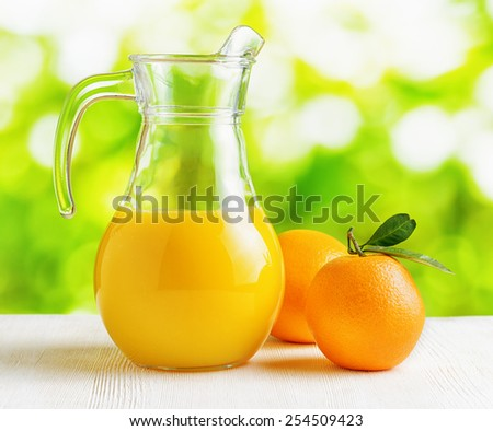 Jug of orange juice and oranges on nature background. Eco food rich in minerals and vitamins. Product of organic farming.
