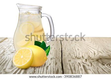 Jug or pitcher of lemonade with lemons on foreground standing on wooden table. Clipping paths for both background and pitcher, infinite depth of field