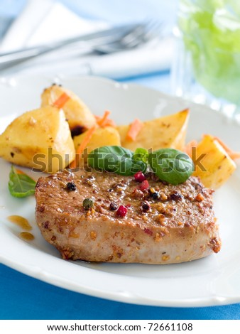 Juicy fillet steak with fresh basil and peppercorns, potato and carrot