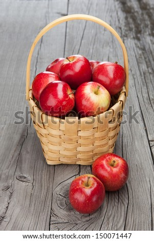 Juicy fresh apples in basket on dark wooden background