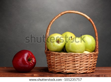 green and red apples in basket. juicy green apples in basket and red apple on wooden table gray background