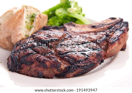 juicy grilled rib steak with baked potato and vegetables