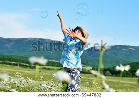 jumping little boy wants to catch soap bubbles