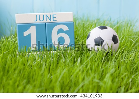 June 16th. Image of june 16 wooden color calendar on green grass background with football outfit. Summer day