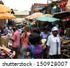 KAMPALA, UGANDA - SEPTEMBER 28, 2012.  A white woman walks away through a market shopping among locals in Kampala, Uganda on September 28,2012. - stock photo