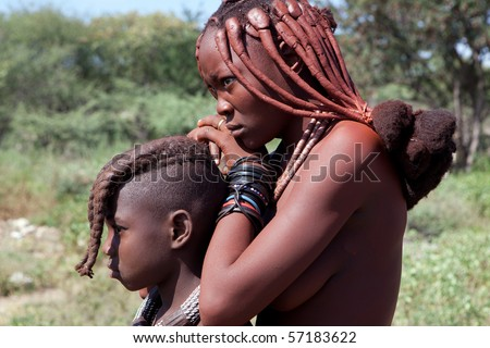 KAOKOLAND, NAMIBIA - MAY 9: An unidentified woman and child with Himba ethnic hairstyles wait for folk art products trade to begin on May 9 2010, in Himba Village near the Kamanjab, Namibia