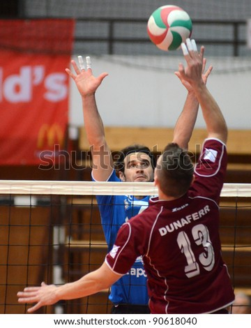 KAPOSVAR, HUNGARY - DECEMBER 9: Andras Geiger (in blue) in action at a Hungarian volleyball National Championship game Kaposvar (blue) vs. Dunaferr (claret), on December 9, 2011 in Kaposvar, Hungary.