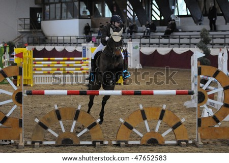 KAPOSVAR, HUNGARY - FEBRUARY 28: An unidentified competitor jumps with her horse on the Winter Jumping Indoor Tournament, February 28, 2010 in Kaposvar, Hungary.
