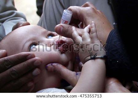 KARACHI, PAKISTAN - AUG 29: Anti polio campaigner administrating vaccine to infant, in  Mehmoodabad area on August 29, 2016 in Karachi.