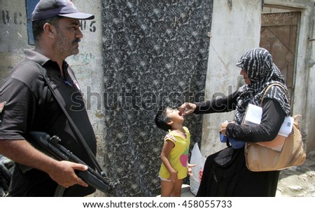 KARACHI, PAKISTAN - JUL 25: Anti polio worker administrating vaccine to the children during campaign run in Bilal Colony area of Korangi locality on July 25, 2016 in Karachi.