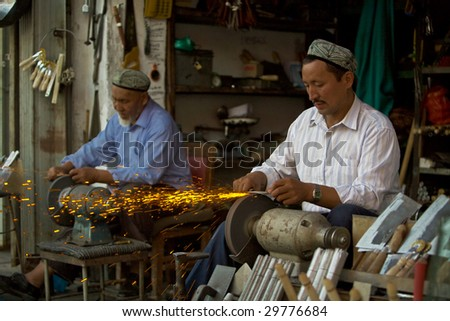 KASHGAR, CHINA - OCT 2: Sparks fly as 2 Uyghur craftsmen resume work after Ramadan sharpen knives on grinding wheels October 2, 2008 in Kashgar, Xinjiang province western China.