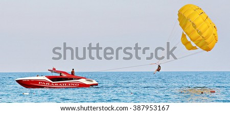 KEMER, TURKEY - AUGUST 14, 2015: Parasailing in a blue sky near sea beach. Parasailing is a popular recreational activity among tourists in Turkey. For editorial use only.