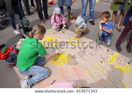 "Kharkiv, Ukraine - April 17, 2016: Children drawing on a huge piece of paper during festival ""Day of a single street"" on Art Street."
