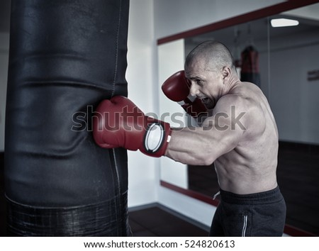 Kickbox fighter training in a gym with punch bags, see the whole series