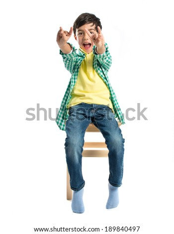 Kid doing the horn sign on wooden chair