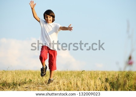 Kid having happy carefree time on yellow wheat field