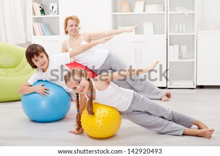 Kids exercising with their mother using large gymnastic balls