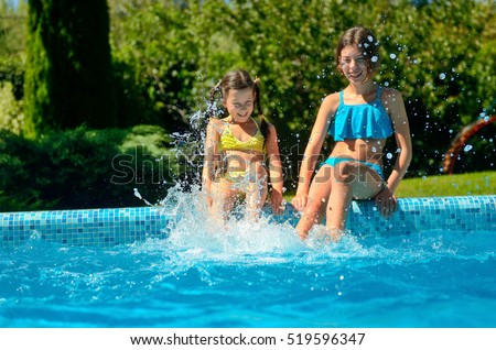 Kids in swimming pool have fun, girls splash in water, happy active children on family vacation