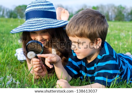 Kids on the meadow looking to dandelion with a magnifying glass