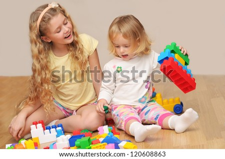 Kids playing with wooden blocks laying on the floor in their room