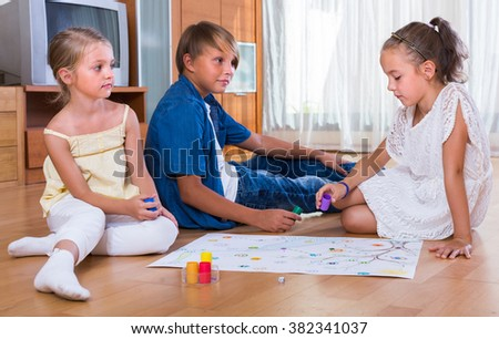 Kids sitting on floor at home with board game and dice