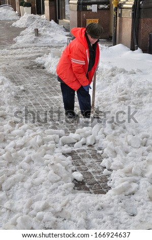 KIEV, UKRAINE � CIRCA MARCH 2013: Unknown street cleaner cleans streets of the city from snow captivity after snowstorm circa March 2013 in Kiev, Ukraine.