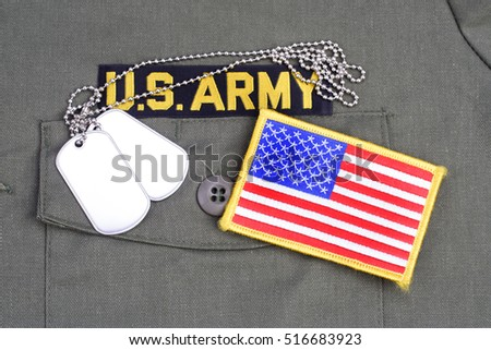 KIEV, UKRAINE - July 20, 2016. US ARMY Branch Of Service Tape with dog tags and flag patch on olive green uniform